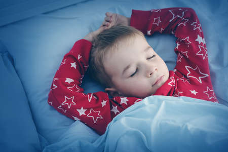 Sleepy boy lying in bed with blue beddings. Tired child in bedroom
