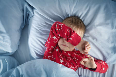 Sleepy boy lying in bed with blue beddings. Tired child in bedroom. Little kid lying awake in red pajamas with toothache