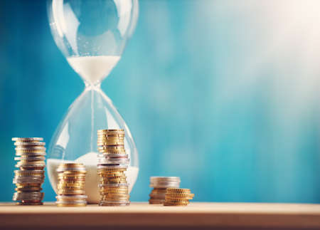 clock with stacked coins and hourglass on blue background