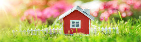 red wooden house on the grass in garden
