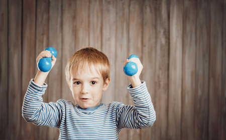 Child holding dumbbells indoors on wooden background. Фото со стока