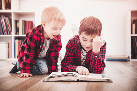Three years old child and his older brother sitting among books at home