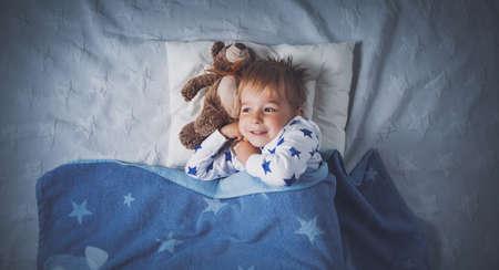 three years old child sleeping in bed Foto de archivo