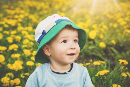 Little boy in hat standing on the field