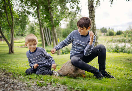 Two angry brothers fighting in park outdoors