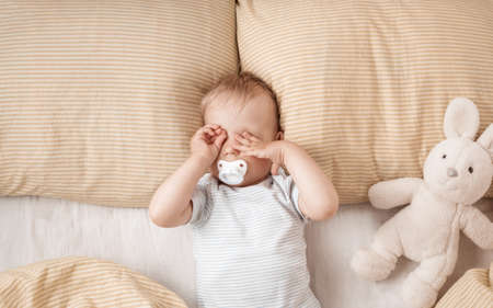 One year old baby in the bed Standard-Bild