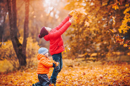 children throwing leaves in beautiful autumnal day. Boys playing outdoors in the park