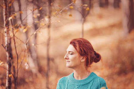 Pretty woman with red hair in autumn forest.