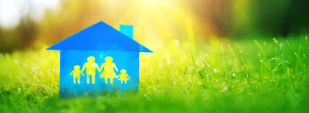 Blue family house is on green grass on a sunny day. Model of a housing with a shape of the family of two parents and two children. Stok Fotoğraf