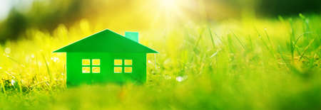 Green house on fresh grass on a sunny day. Model of a family housing standing on the meadow. Stok Fotoğraf