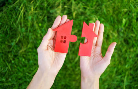 Model of small red house in the human hand. Concept of funding, buying, selling and renting.