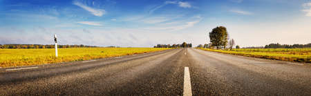 Asphalt road panorama in countryside on sunny autumn day. Road with dividing lines.