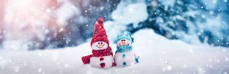 little knitted snowmans on soft snow on blue background Stok Fotoğraf