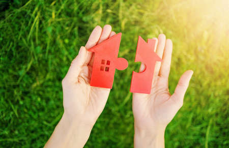 Red house with a shape of two parts of puzzle in human hands. Concept of apartment renting, buying and selling.