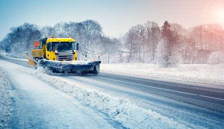 Snow plow truck clearing snowy road after snowstorm. Zdjęcie Seryjne
