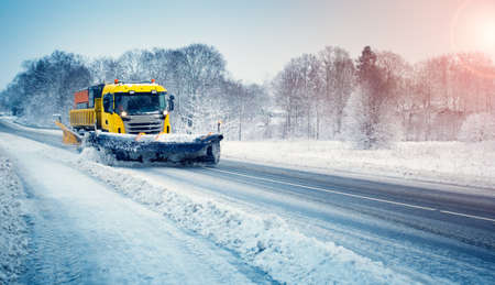 Snow plow truck clearing snowy road after snowstorm. Banco de Imagens