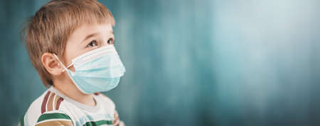 Boy in medical face protection mask indoors on blue background 写真素材