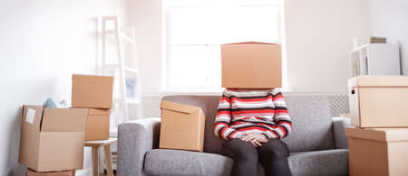 Tired womanwith cardboard box on her head sitting on the sofa in her new house.Concept of renting, moving in new house and buying an real estate.