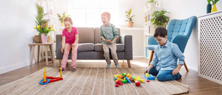 Playful children sitting in the living room on the Birthday party. Banque d'images