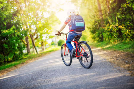 Teenager on the bicycle at the asphalt road riding to the school Banque d'images