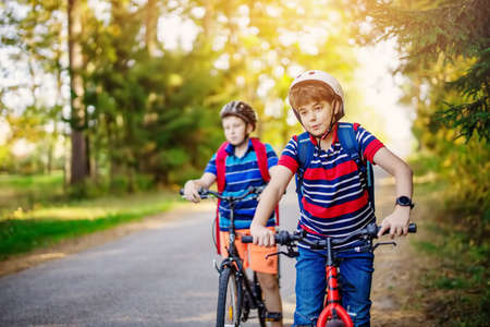Teenagers on the bicycles at the asphalt road riding to the school