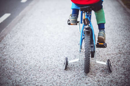 Little boy on the bicycle on the road in the city.