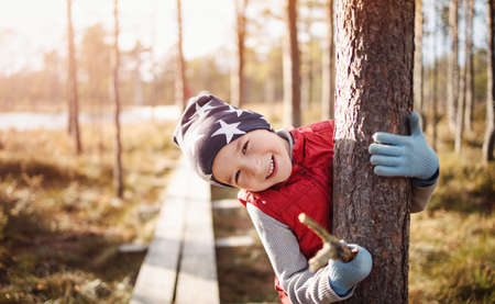 Cute boy in the forest hugging a trees trunk