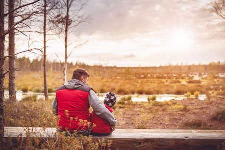 Father with son sitting on the bench on the Estonian bogs.