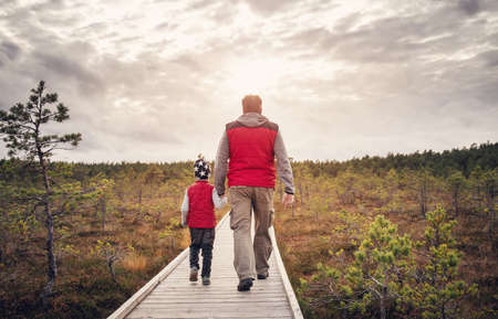 Father with son walking on the path on the Estonian bogs. Banque d'images