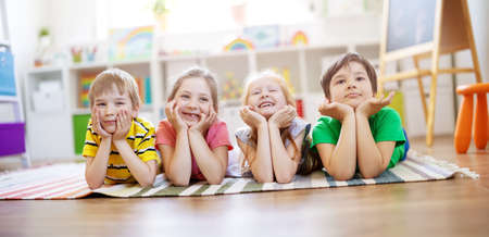 Group of children lying on the floor and looking in the camera. Banque d'images