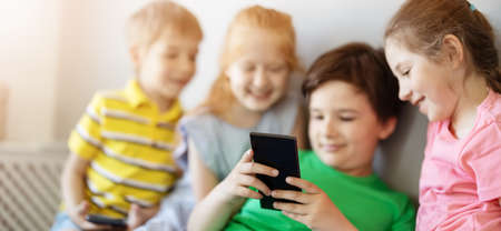 Group of children sitting indoors and looking in the smartphone