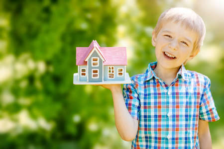 Little child holding in his hand a model of the house.
