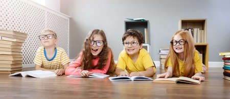 Four cute children in glasses lying on the floor indoors with books