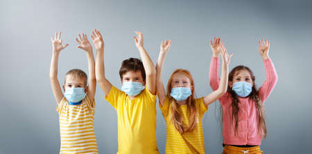 Group of four children in medical mask standing indoors with holding hands up.