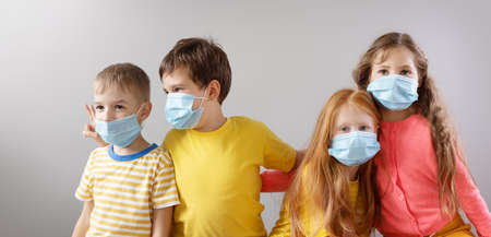 Group of four children in medical mask standing indoor. Banque d'images