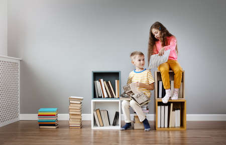Two children sitting in the room and reading books