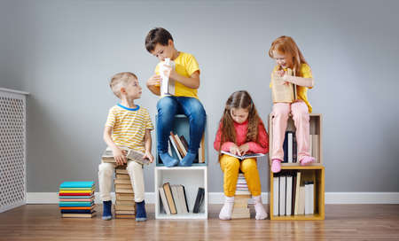 Group of children sitting on the books stacks and on the bookshelves in the room and reading periodical.