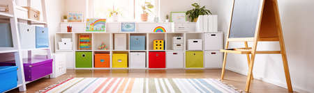 White nursery room with shelves and colourful boxes. Banque d'images