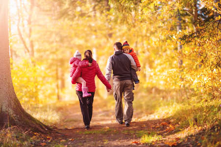Family walking along the footpath in the autumnal natural park