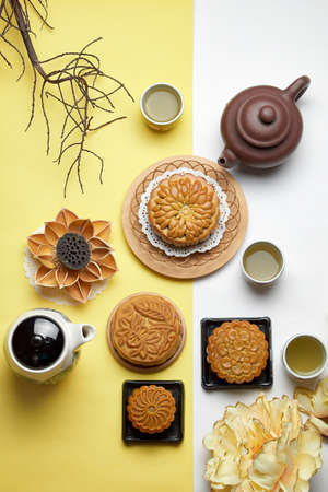 Mid autumn Festival. Chinese traditional moon cake and tea isolated on yellow and white background