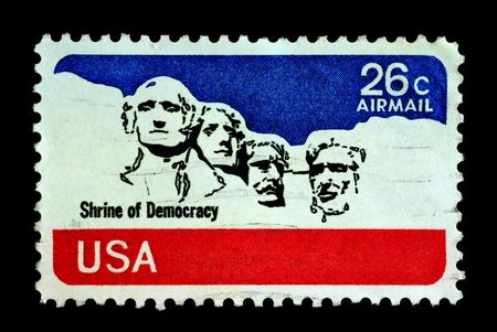 Shrine of democracy on USA stamp featuring mount rushmore national memorial . Stone Sculptures of George Washington, Thomas Jefferson, Theodore Roosevelt, and Abraham Lincoln.
