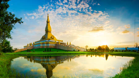 reflect: Thai pagoda in golden light with reflect on water.