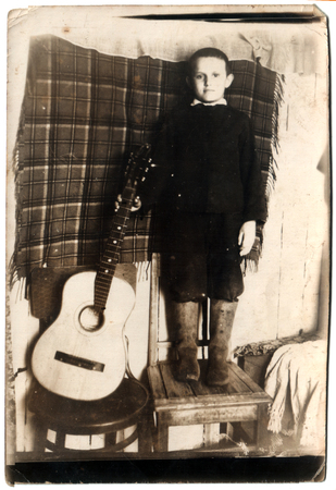 USSR - CIRCA 1962  little boy with a guitar standing on chair, circa 1962