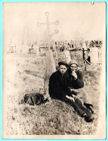 USSR  - CIRCA 1930s: Grand mother with her grand son sitting on grave
