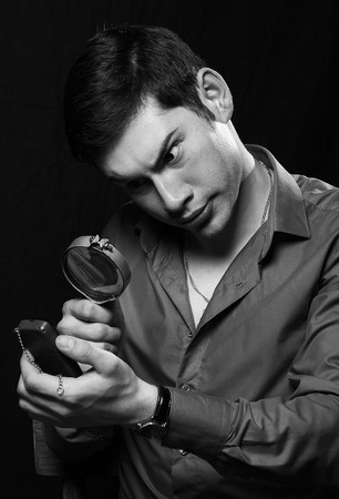 portrait of young man looking through a magnifying glass over black background photo