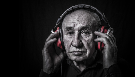 Studio portrait of an old man in headphones photo