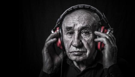 Studio portrait of an old man in headphones 版權商用圖片