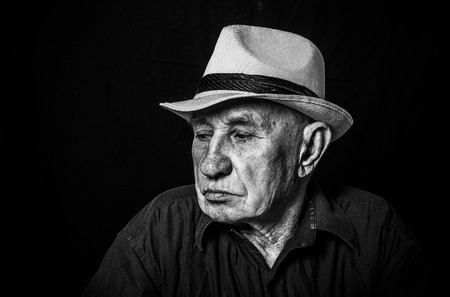 Artistic portrait of an old man in a hat photo