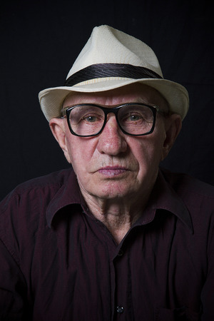 Artistic portrait of an old man with glasses and hat photo