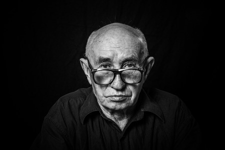 Artistic portrait of an old man with glasses